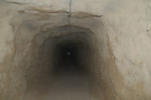 der ca. 100 Meter lange Tunnel ca. 2 Meter hoch, stockdunkel. Am Ende sieht man ein kleines Licht, der Ausgang