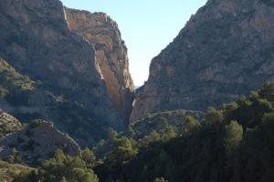 man sieht über ein Tal die letzte Schlucht des Weges. An der rechten Felswand erkennt man den Holzplanken des Weges in 100 Meter Höhe.