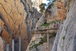 Einige Wanderer die eng an die Felswand gepresst gehen