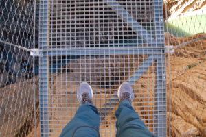 Meine Füße auf dem Stahlgitter der Brücke, Blick in den Abgrund