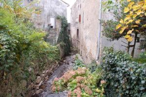 Eine Bach, der zwischen zwei sehr alten Häusern hindurchfließt.