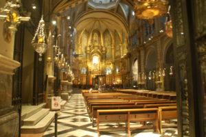 """Man sieht die Basilika innen. Vorn über dem Altar (schlecht zu erkennen) sieht man ein helles Licht. Dort steht die """"schwarze Madonna""""."""