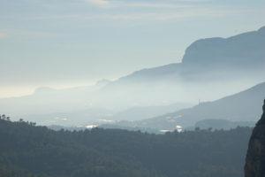 Man blickt auf Berge beim Tal von Pop. Im Tal erkennt man weiße Flächen, Gewächshäuser.