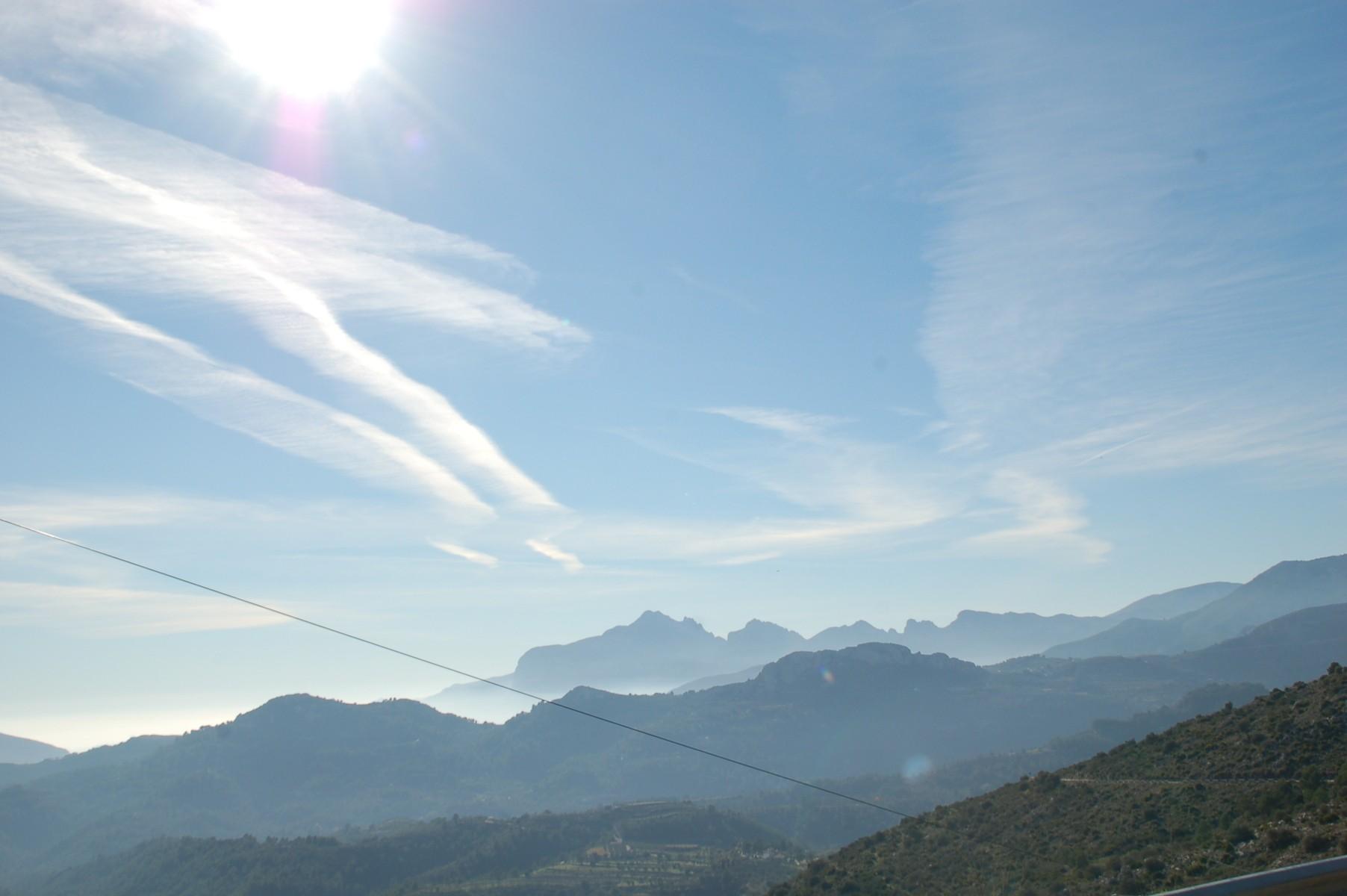Man blickt über Berge und erkennt einen leihten Dunstschleier im Tal
