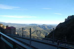 Maan blickt vom Kloster über die Gleise der Zahnradbahn am Steilhang in das Tal.