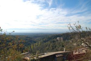Man blickt in das Tal vom französchien Schwarzwald aus und sieht im Hintergrund die Pyrenäen. Das Chateau steht im Vordergrund unten rechts im Bild.