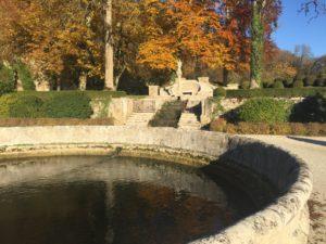 Ein Wasserbassain am Ende des Parks. Es wird durch einen Bach gespeisst, der am hinteren Ende über eine gemauerte Treppe herabfällt. Auf der Wiese darüber stehen Laubbäume in gelb, rot und braun