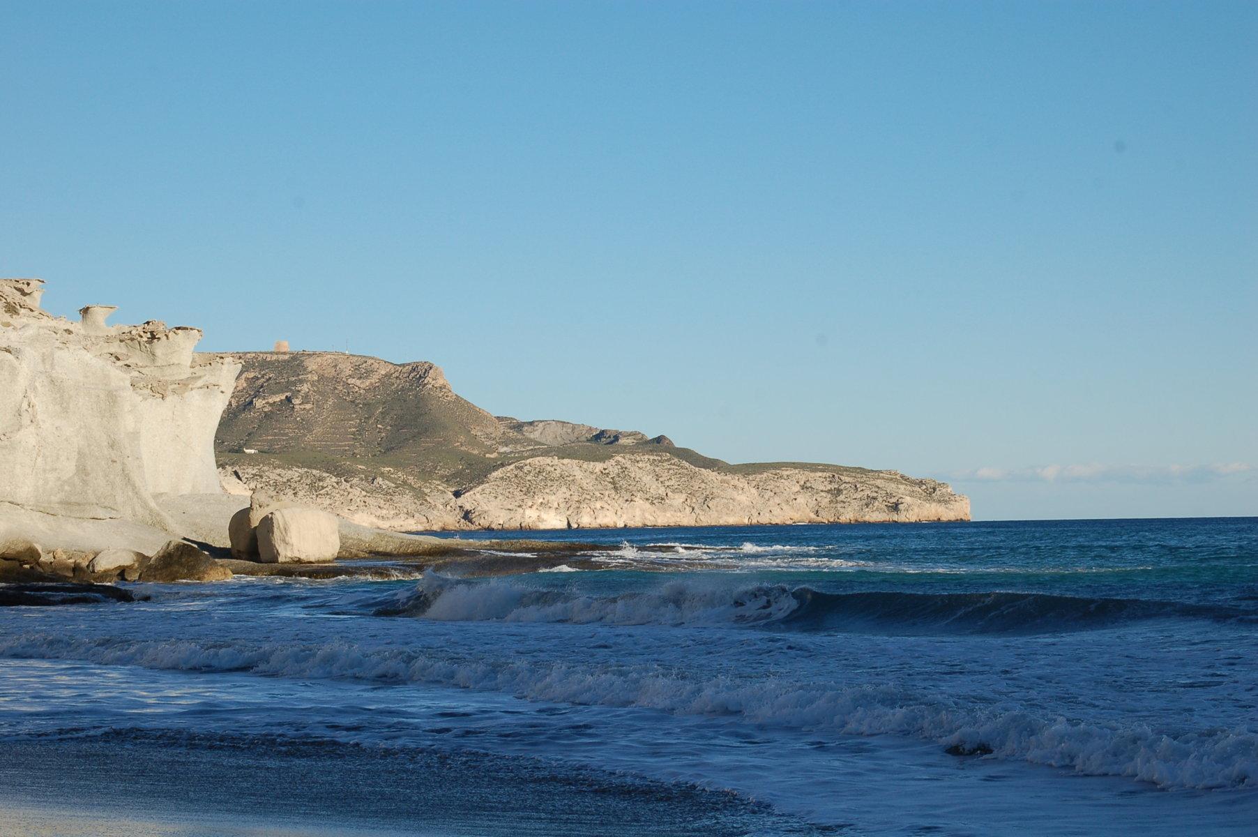Wellen rollen an den Strand, im Hintergrund ein etwa 50 Meter hoher Felsen unter wolkenlosem Himmel