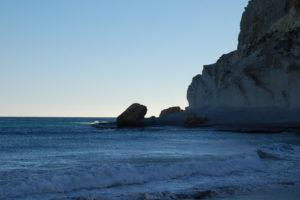 Ein Felsen im Meer an den die Brandung schlägt unter blauem Himmel.