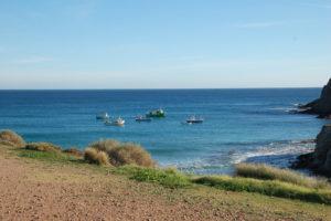 Einige kleine Fischerboote dümpeln vor dem Strand auf dem Meer unter wolkenlosem blauen Himmel.