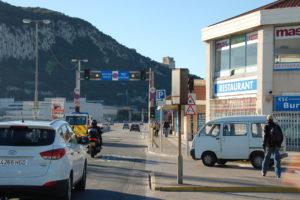 Die Straße in das Zentrum von Gibraltar. Eine Ampel stellt sich auf Rot, wenn ein Flugzeug startet.