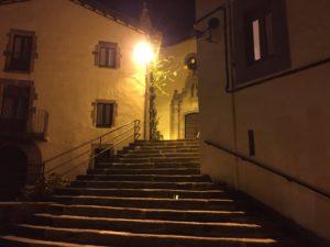 Eine Treppe führt zu Portal der kleinen Stadtkirche im Laternenlicht.