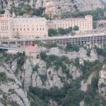 Man sieht das eindrucksvolle Benediktinerkloster Montserrat von einem gegenüberliegenden Felsvorsprung