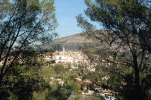 Man sieht die Stadt Parcent im Tal von Pop durch Bäume.