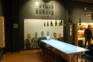 """Das Plakat zeigt sechs Männer, die Betreiber der Weinkellerei """"Artcava""""."""