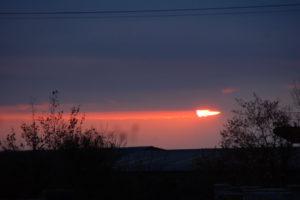 Die größtenteils durch Wolken verdeckte Sonne lässt den Abendhimmel rot orange leuchten.