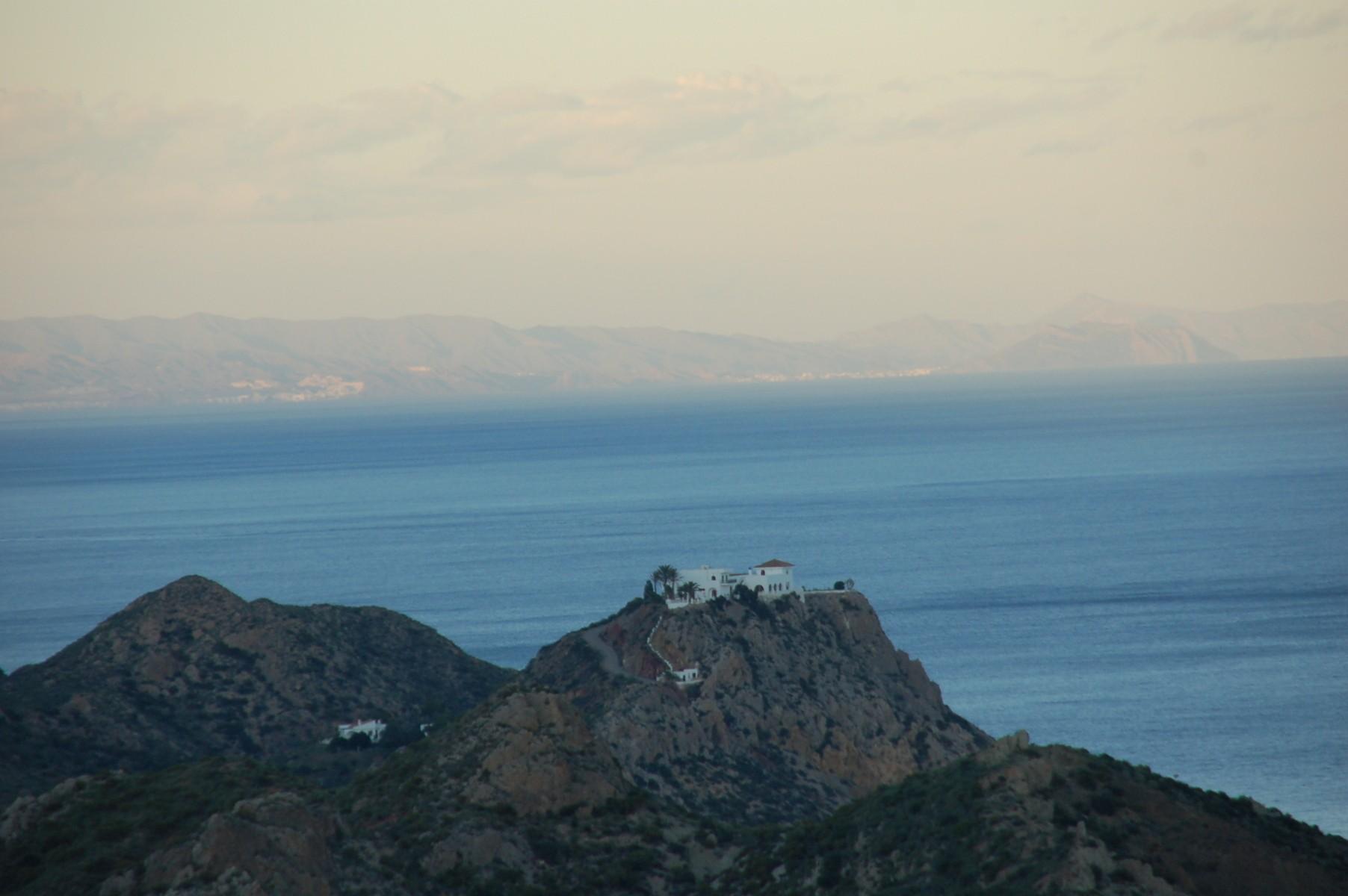 Man sieht im Abendhimmel ein einsames typisch für Andalusien weiß getünchtes Haus in einer schroffen felsigen Umgebung, im Hintergrund das Mittelmeer