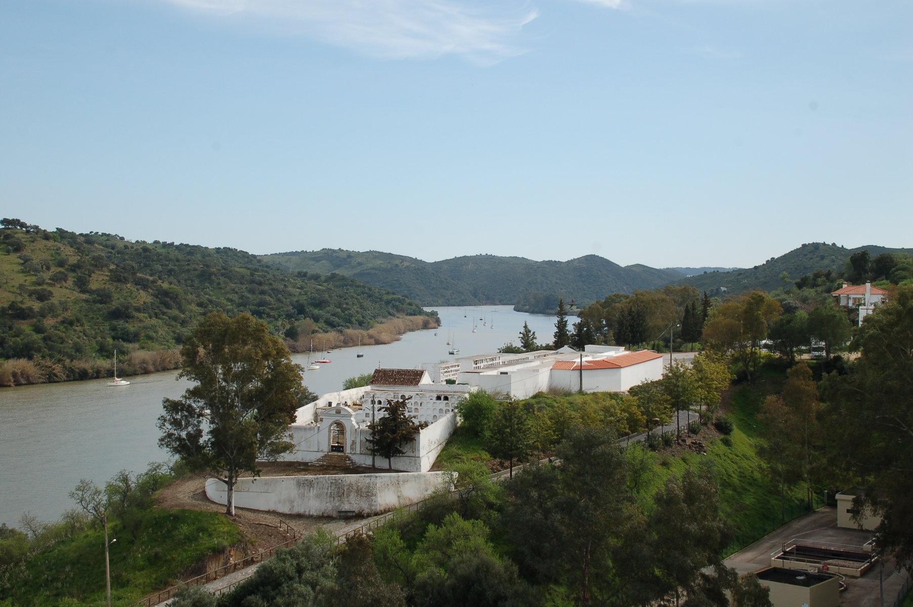 im Vordergrund einige weiß getünchte Gebäude am Flussufer des Guadiana