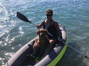 Eva sitzt in ihrem Kajak und ihr Hund Teo zwischen ihren Beinen