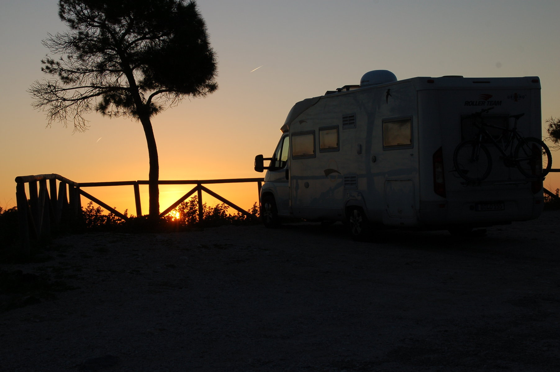 Das Womo ist auf einem Plateau etwa 50 Meter über dem Meer geparkt. Im Hintergrund sieht man die untergehende Sonne.