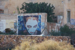 Eine Wandmalerei in Rodalquilar: Ein ünbergroßes Gesicht sieht leicht nach untern und ist weiß bemalt.