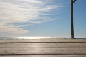 man sieht vor leicht bewölktem Himmel eine  Holzplattform vor dem Meer. Die Sonne spiegelt sich etwas im Meer