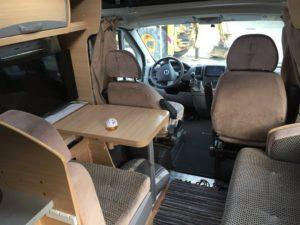 Das Bild zeigt von hinten fotografiert den Esstisch mit quer eingebauter Couch. Links am Rand der Fernseher und im Hintergrund das Fahrerhaus.