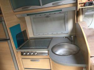Ausstattung der Küche des Wohnmobiles: Rechts die Spüle, in der Mitte ein abgedecktes 4-fach Gaskochfeld, links sieht man ansatzweise den Kühlschrank