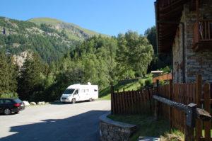 Das Wohnmobil ist am Waldrand geparkt. Der Untergrund ist schräg, weshalb die Vorderräder auf Plastikrampen stehen, um das Gefälle auszugleichen. Im Hintergrund sieht man die Schweizer Alpen.